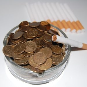 Cigarette with ash tray full of coins